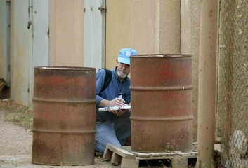 U.N INSPECTOR EXAMINES OIL DRUMS AT ANIMAL VACCINE PRODUCTIONLABORATORY IN DOURA.