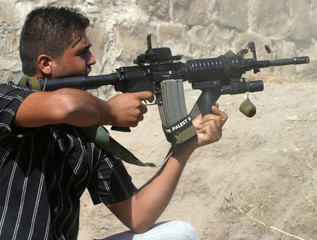 Palestinian gunman takes position during clashes with Israeli troops in Qabatiya
