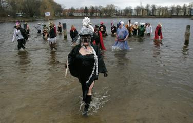 Members of Berlin's ice swimming club 'Berliner Seehunde' take a dip in the water of lake Orankesee during their 23rd carnival swimming in Berlin