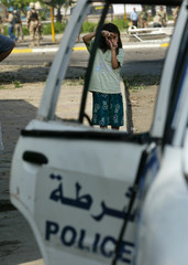 A little girl looks immune as she pretends to take picture of a police car that was destroyed by a ...