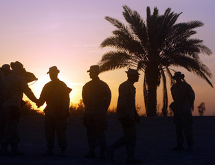 SILHOUETTE OF US SOLDIERS AT EARLY MORNING CEREMONY TO AWARD PURPLE HEART MEDALS AT CAMP BAHARIA.