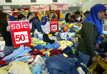 Indonesian shopkeepers serve customers during a Ramadan sale in one of Jakarta's busiest shopping ...