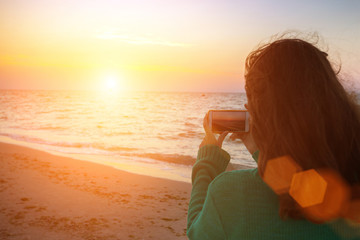 girl is taking pictures of the sunrise at sea
