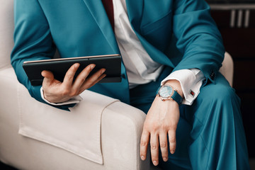 Businessman keep a digital tablet in hand whilst sitting on a sofa in a blue suit. on hand expensive mechanical watch with leather strap. shirt with cufflinks