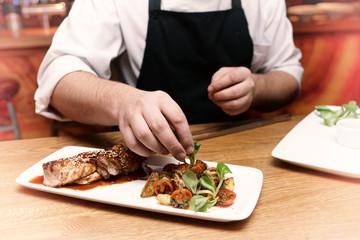 Chef is decorating chicken teriyaki dish, toned