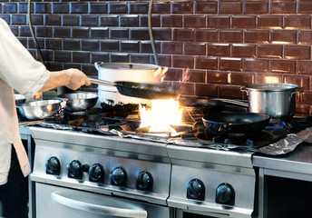 Chef is making flambe dish in restaurant kitchen, toned