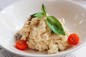 Creamy risotto in porcelain plate, toned