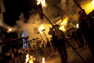 Villagers light torches before the start of the Divina Pastora procession in Casarabonela, southern Spain
