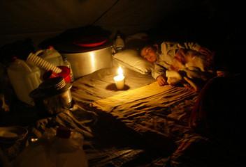Pakistani child who survived earthquake sleeps inside a tent in Balakot