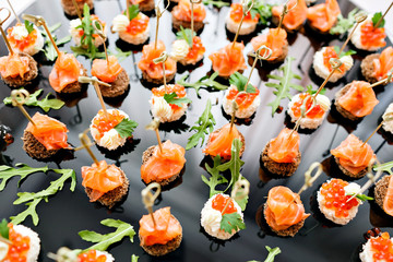 the buffet at the reception. Assortment of canapes. Banquet service. catering food, snacks with salmon and caviar. rye, wheat bread. selective focus