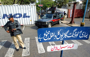 PAKISTANI POLICE GUARD A STREET BLOCKED WITH CARGO CONTAINERS NEAR THEAMERICAN CONSULATE IN KARACHI.