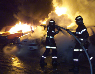 Firemen extinguish burning cars during new year's eve in Strasbourg northern suburb of Cronenbourg J..