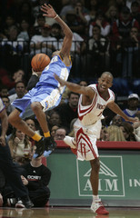 Denver Nuggets guard Allen Iverson is sent reeling as he is fouled by Houston Rockets guard Rafer Alston in Houston