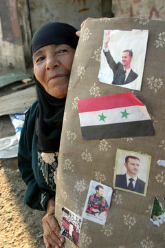 Bedouin woman holds furniture with pictures of Syrian President Bashar al-Assad, in a former Syrian ...