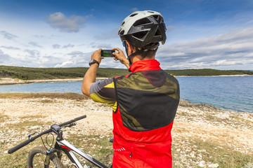 Mountainbiker am Meer macht ein Foto mit dem Smartphone