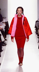 A model wears a red dress, red coat with pink lining and red boots as she walks the runway at a show..