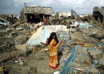 Indian woman weeps among debris and damaged houses hit by Sunday's tsunami at Nagapattinam beach.
