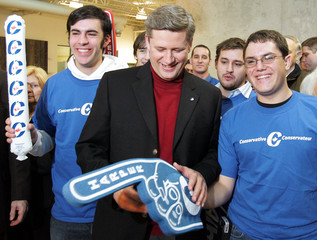 Conservative Party of Canada leader Harper inspects a supporter's foam hand in Waterloo
