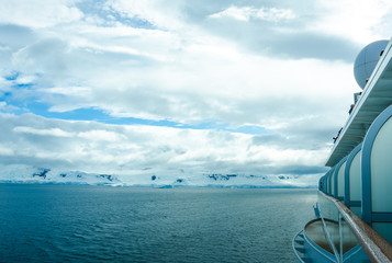 Cruise ship approaches the rocky coast of Antarctica covered with ice and snow on a rare sunny day.