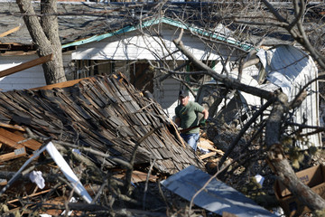 A man clears wreckage left behind in the wake of a tornado in Lone Grove, Oklahoma