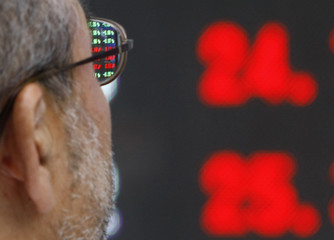 A man looks at an electronic stock index board in Tokyo