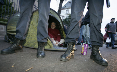 "Member of French association ""Enfants de Don Quichotte"" sits in a tent behind policemen in Strasbourg"