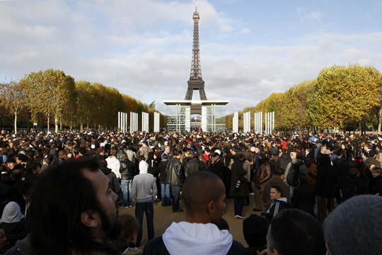 People wait for a bus which is part of a publicity stunt by online marketing company Mailorama.fr, near the Champ de Mars near the Eiffel Tower in Paris