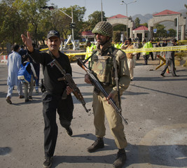 Security forces clear the site of a suicide bomb attack outside Pakistan's naval headquarters in Islamabad