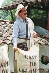 """COLOMBIA'S COFFEE ICON JUAN VALDEZ POSES NEXT TO A BAG CONTAINING """"100 COLOMBIAN COFFEE.\"""