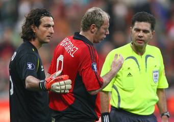 Bayer Leverkusen's Barberez is comforted by CA Osasuna's goalkeeper Ricardo and referee Hauge during their UEFA Cup quarter-final first leg soccer match in Leverkusen