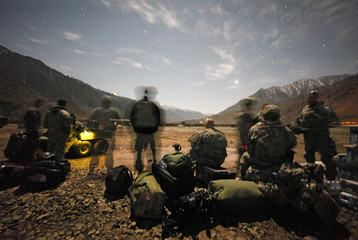 Military and civilian personnel wait in the moonlight for an incoming helicopter at Forward Operating Base Bostick in eastern Afghanistan