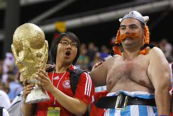 A France fan (R) dressed as the cartoon character Obelix poses with a South Korea fan after the Grou..