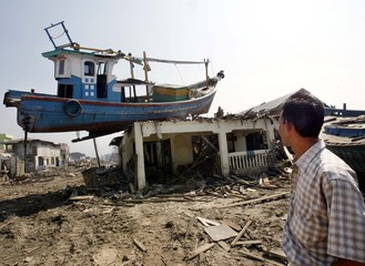 File photo of Acehnese man looking at a boat left on top of house as a result of the tsunami in ...