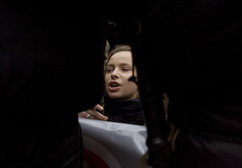 A Belarussian woman sits on the ground blocked by riot police during a protest in central Minsk