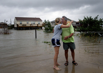 HOMEOWNER HUGS RELATIVE IN FLOODWATERS AFTER HURRICANE ISABEL.