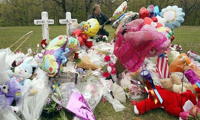 Don Howard places balloons at a memorial for slain girls in Zion.