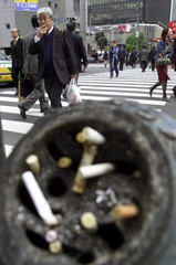 JAPANESE PEDSTRIAN SMOKES BEHIND ASHTRAY STAND IN TOKYO STREET.