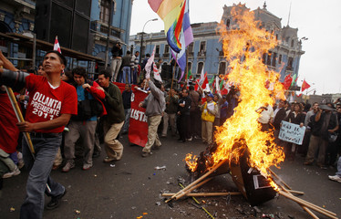 Protesters burn a mock coffin with pictures of Peruvian Ministers march during a nationwide strike in Lima