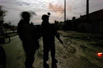 U.S. soldiers from the 1st Infantry Division are silhouetted as they guard a street during a night ...