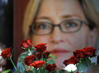 RED ROSES ARE PLACED IN FRONT OF A PICTURE OF SLAIN SWEDISH FOREIGNMINISTER ANNA LINDH IN STOCKHOLM.