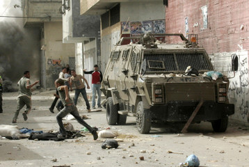 Palestinian stone-throwers run during clashes with Israeli troops near Nablus