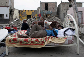 A man reads a newspaper on a bed in front of his destroyed house in Pisco