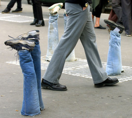 A man walks among sculptures in Paris April 30. The sculptures, made with trousers legs and shoes fi..