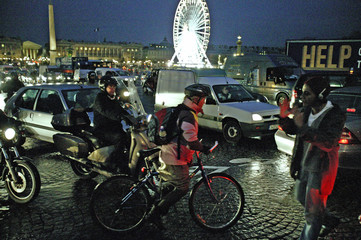 Commuters on foot and bicycles cross Place de la Concorde on their way home from work as transport strikes continue in Paris