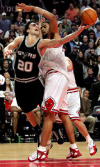 Spurs' Ginobili drives to the basket around Bulls' Chandler during fourth quarter action in Chicago