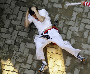 A fallen runner reacts after bull stepped on him and ripped his pants during fourth bull run of San Fermin festival in Pamplona