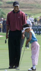 TIGER WOODS PLAYS GOLF WITH YOUNG GIRL AT CHINA'S MISSION HILLS CLUB.