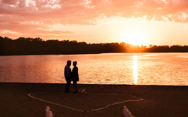 A couple is having romantic moment at a lake under sunset