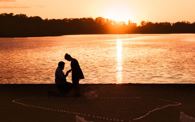A man is proposing to his girl friend at a lake under sunset