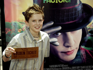 "British actor Freddie Highmore poses with a ""golden ticket"" at the premiere of ""Charlie and the Choc.."